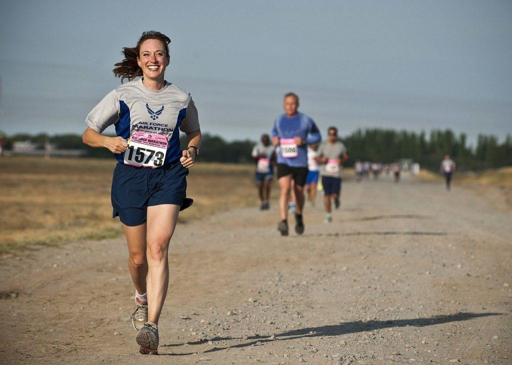 woman running towards camera on a dirt road with a race number, smiling