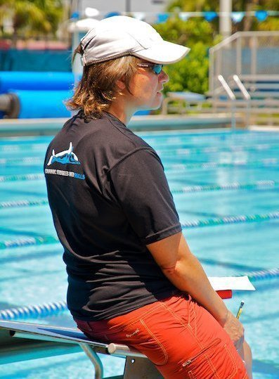 Coach Suzanne Leaning on Diving Block at Poolside