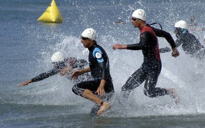 4 male triathletes running and diving into the ocean